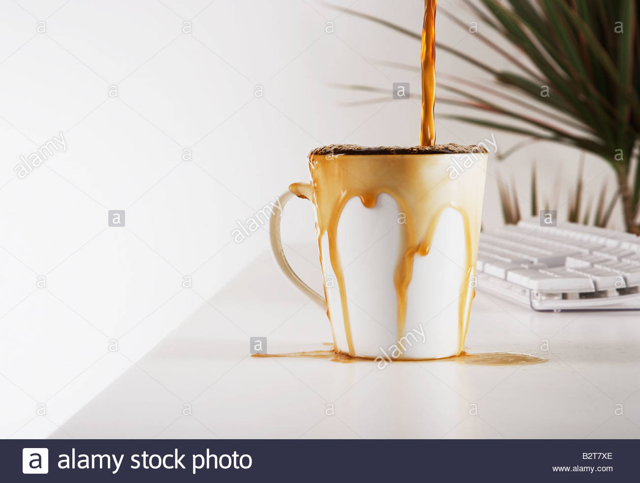 Close up of coffee overflowing cup - Stock Image