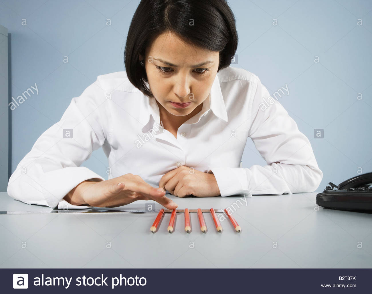 Businesswoman carefully counting pencils - Stock Image