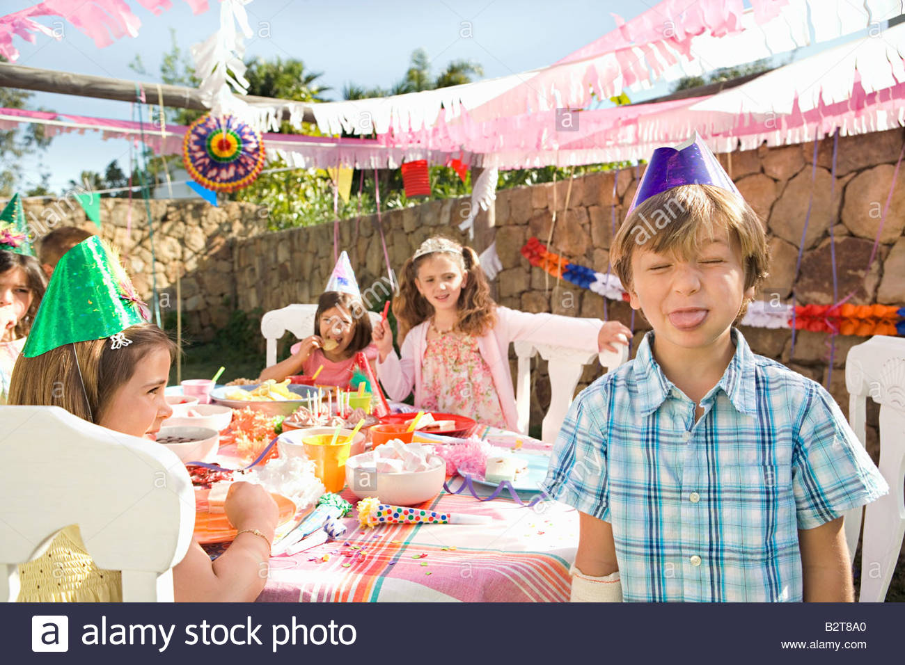 Mischievous young boy at birthday party - Stock Image