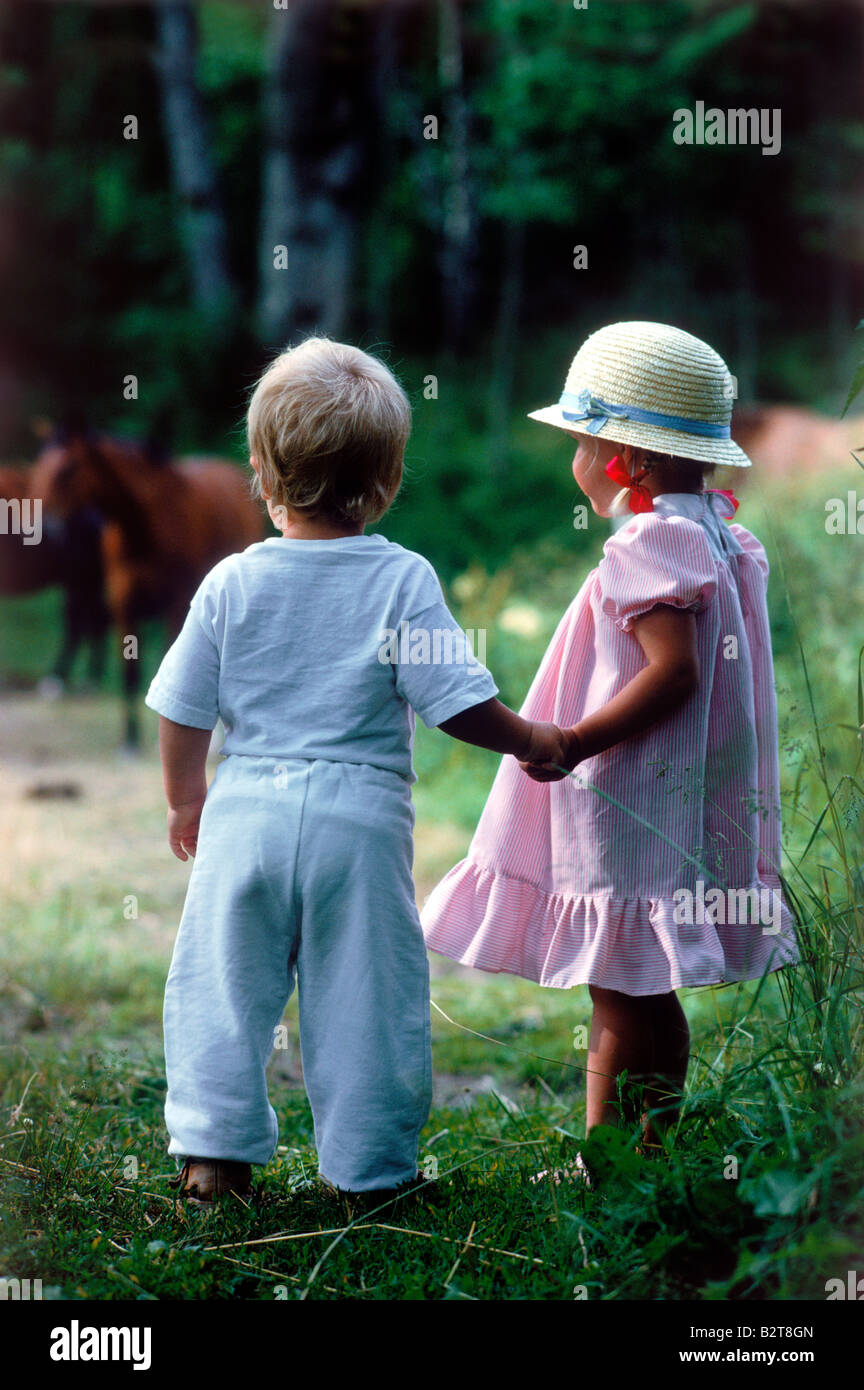 Boy and girl 2-3 years old holding hands in field with horses Sweden summer - Stock Image