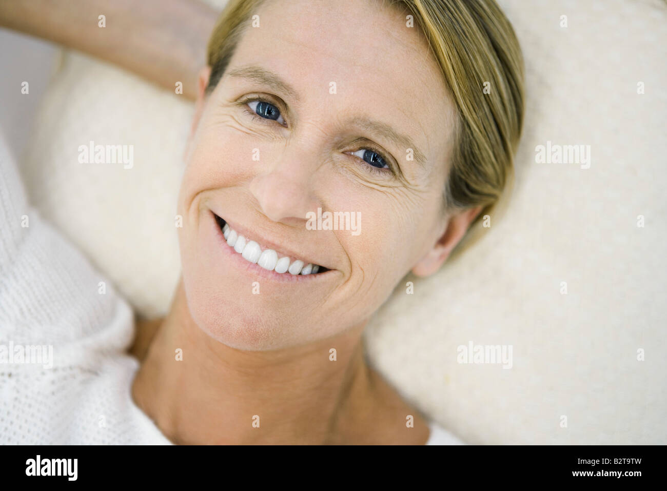 Woman lying on back, smiling at camera, high angle view - Stock Image