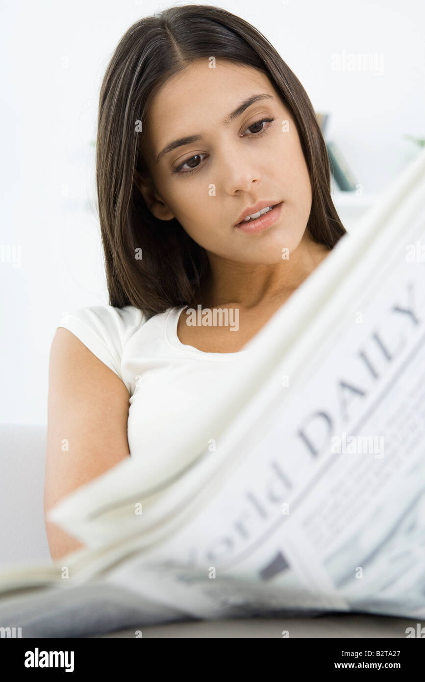 Woman reading newspaper, head tilted - Stock Image