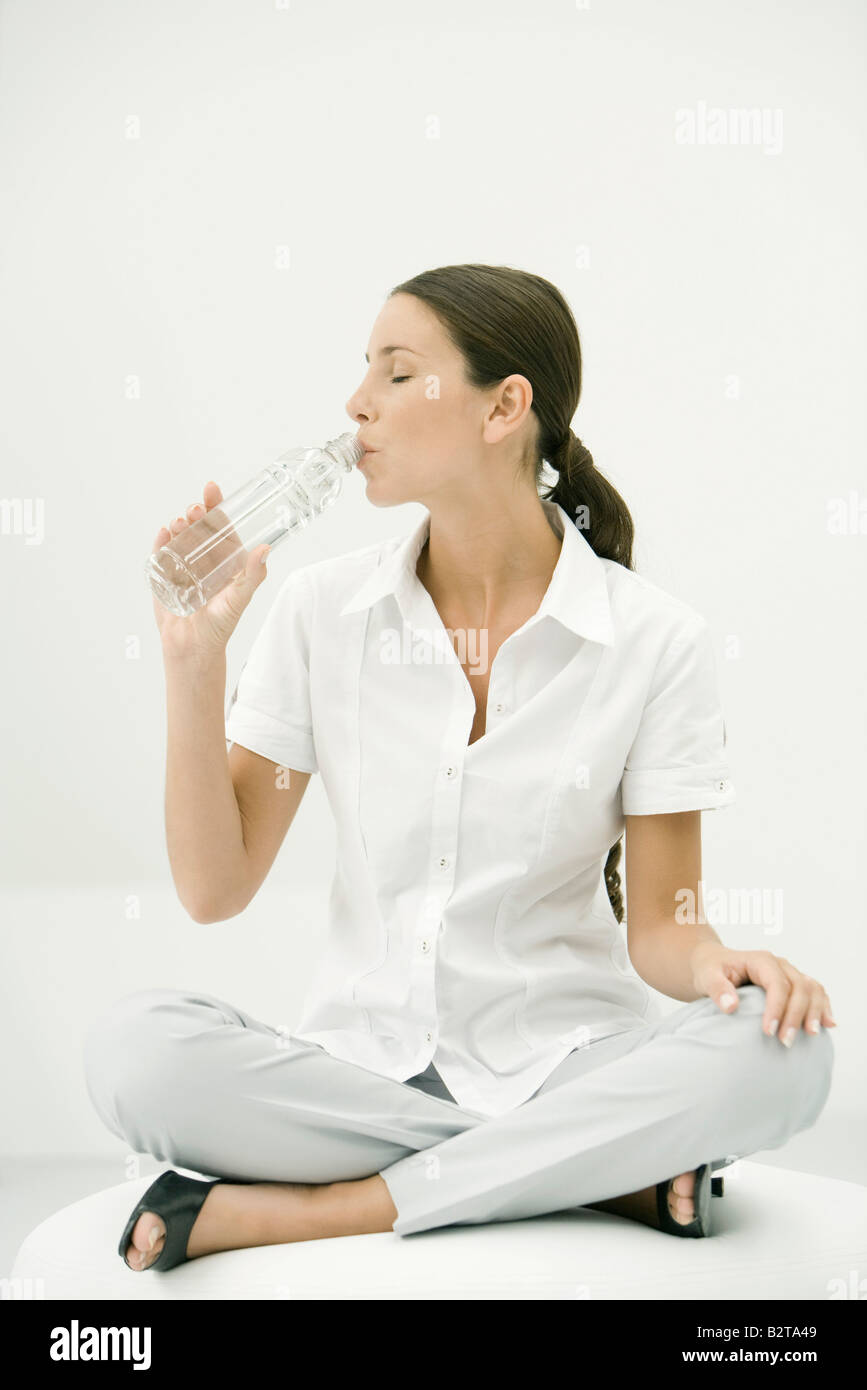 Woman sitting cross-legged, drinking water, eyes closed - Stock Image