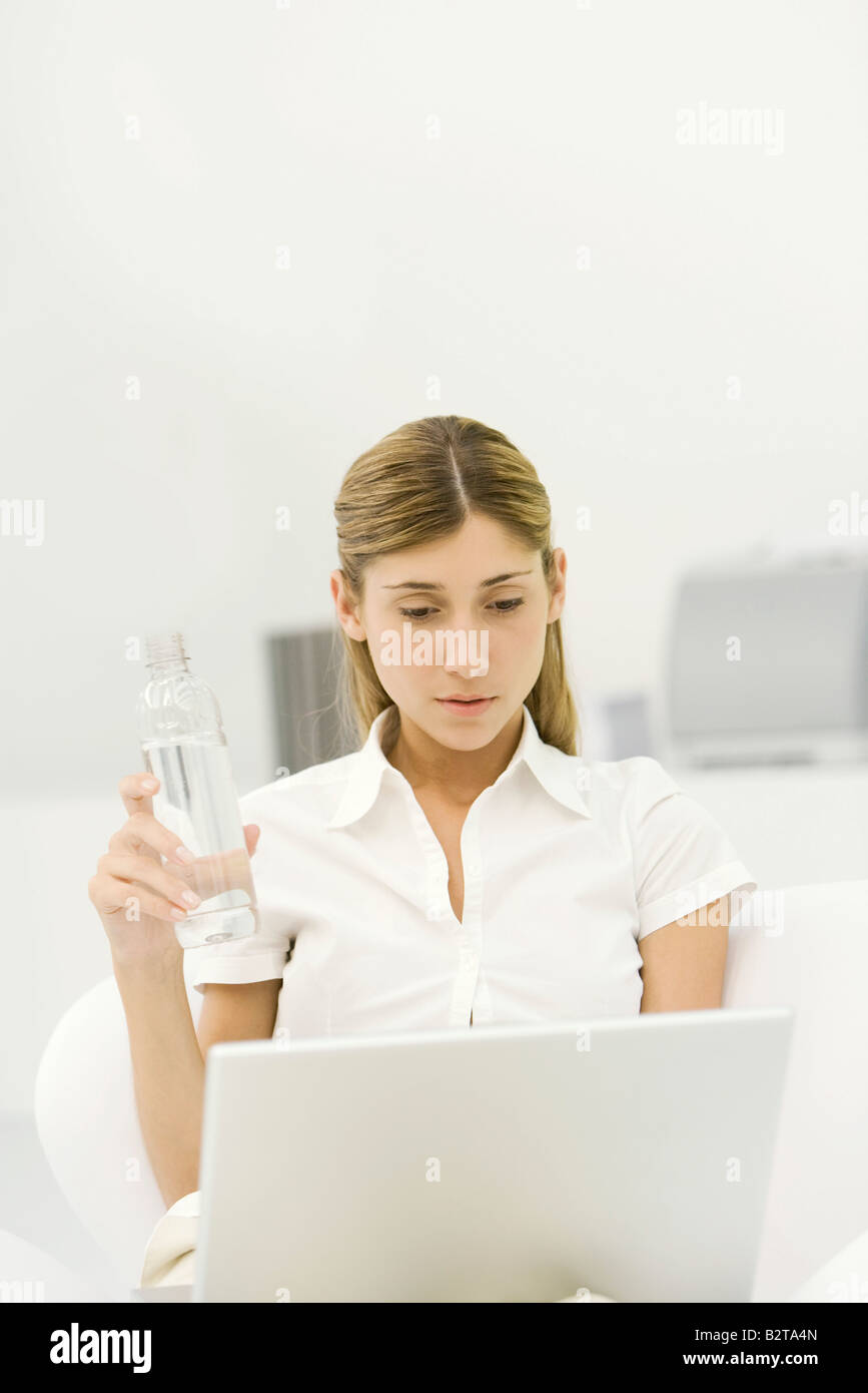 Woman using laptop computer, holding bottle of water - Stock Image