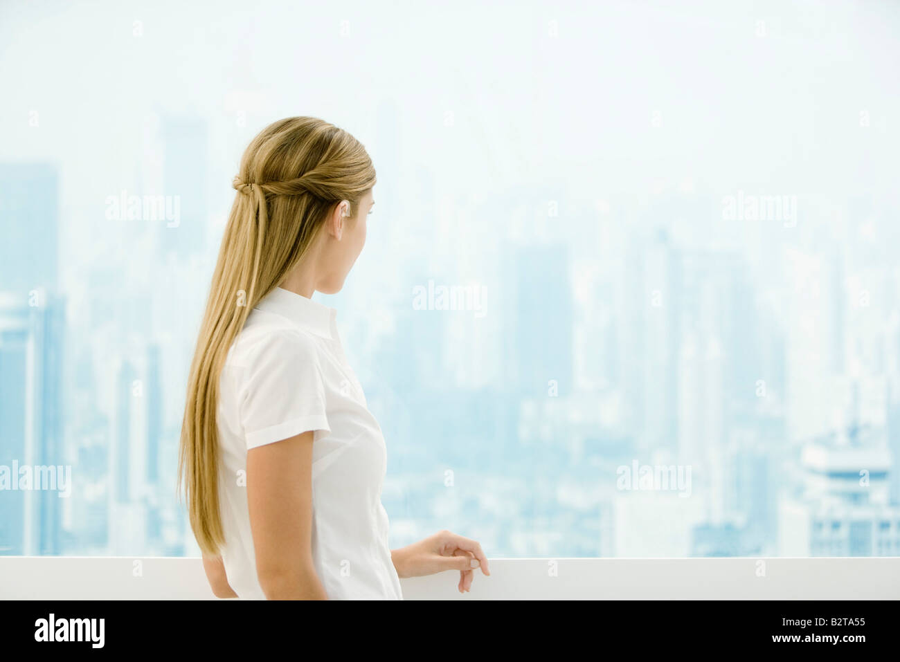 Young woman standing in front window, looking out - Stock Image