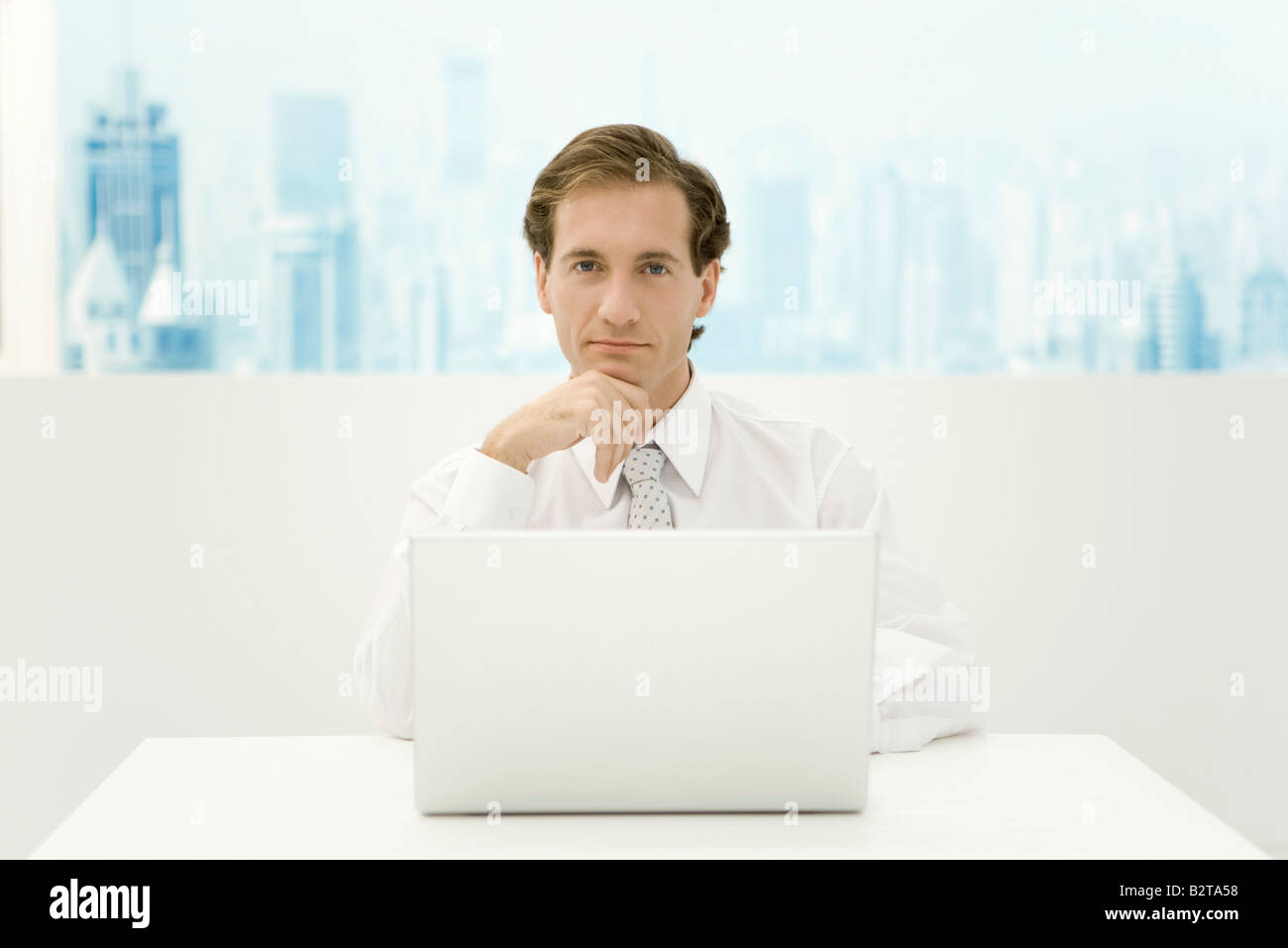 Businessman sitting in front of laptop computer, hand under chin, looking at camera - Stock Image
