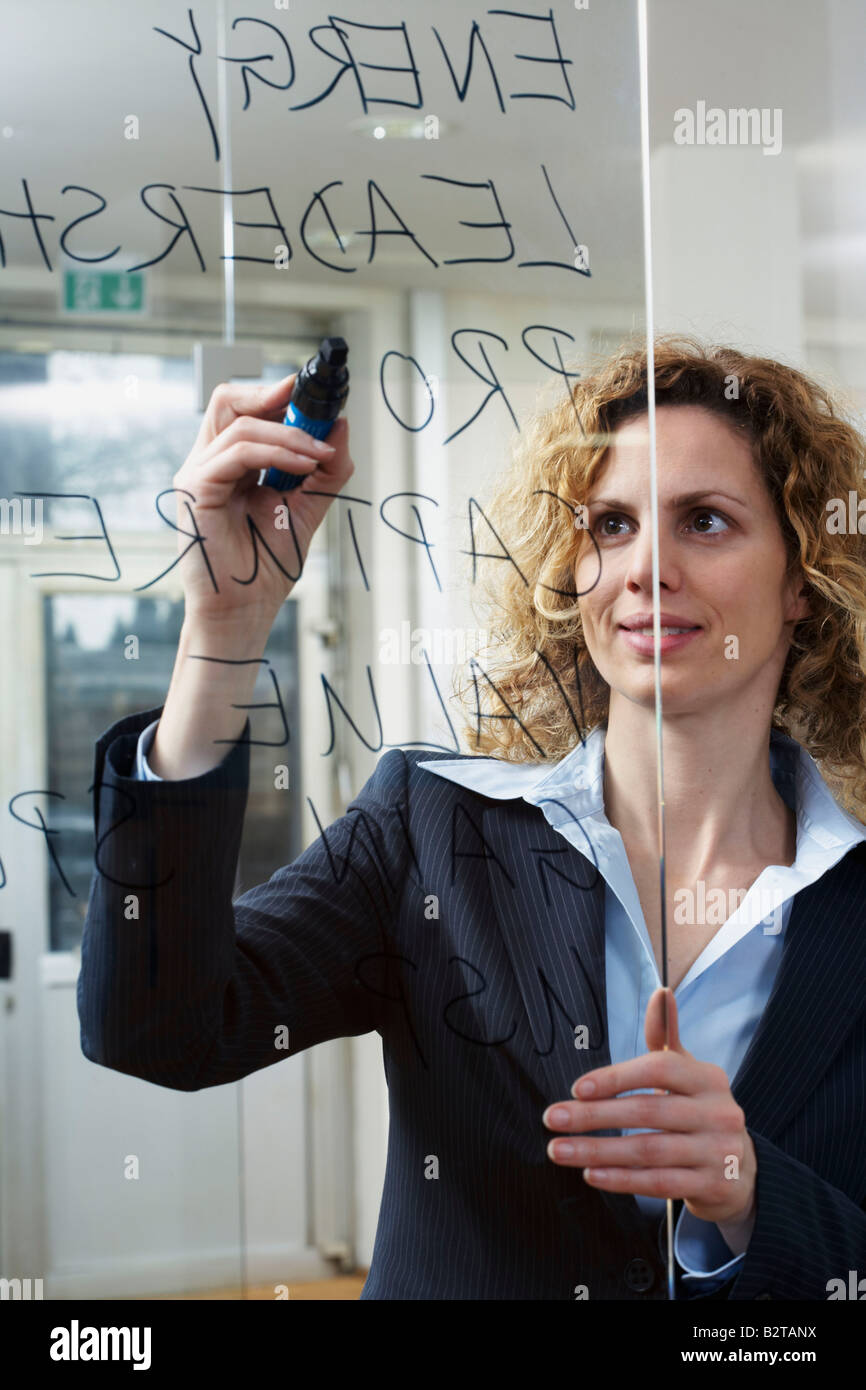Businesswoman writing keywords on glass - Stock Image