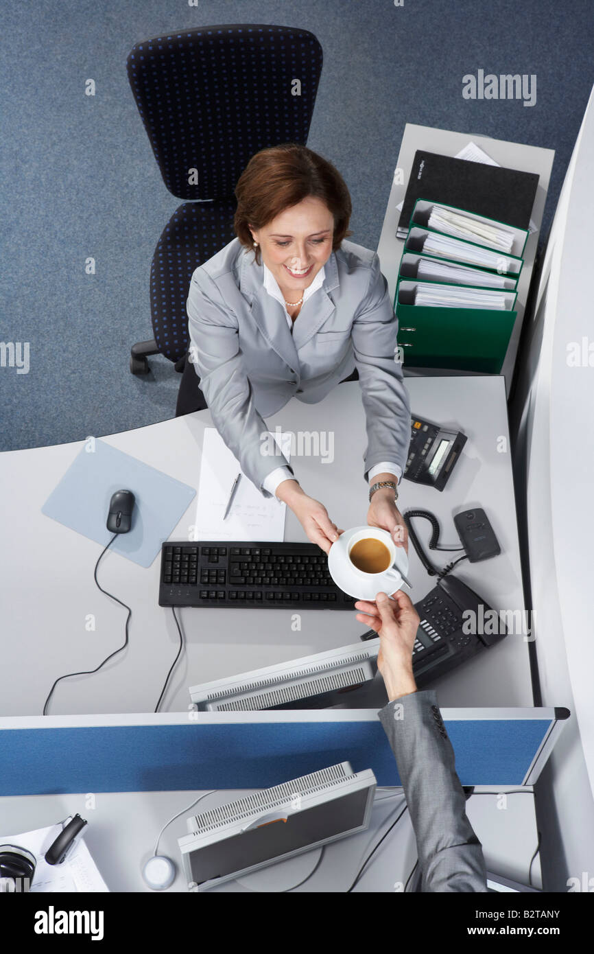 Businesswoman passing a coffee cup - Stock Image