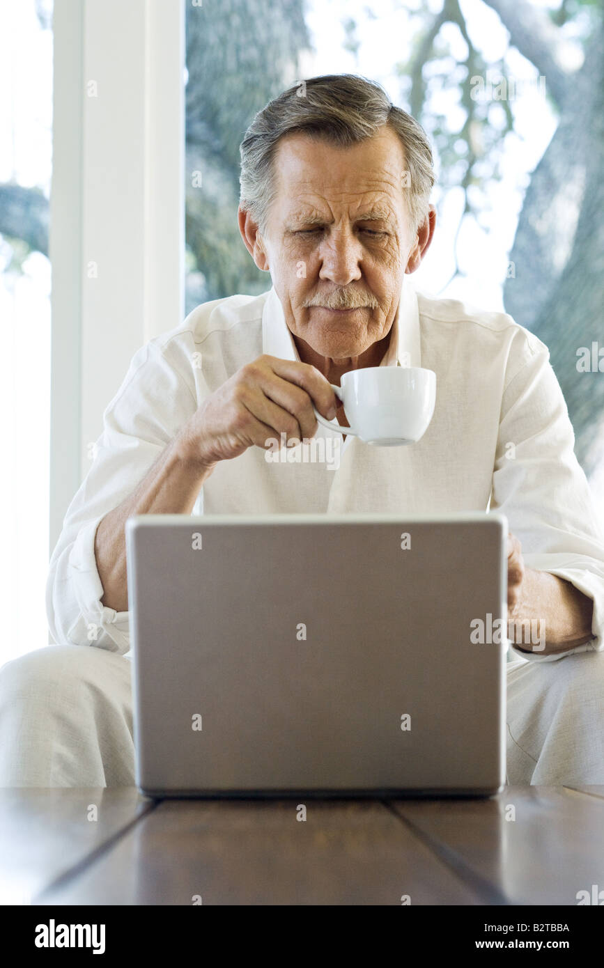 Senior man holding coffee cup, looking down at laptop, sitting with legs apart - Stock Image