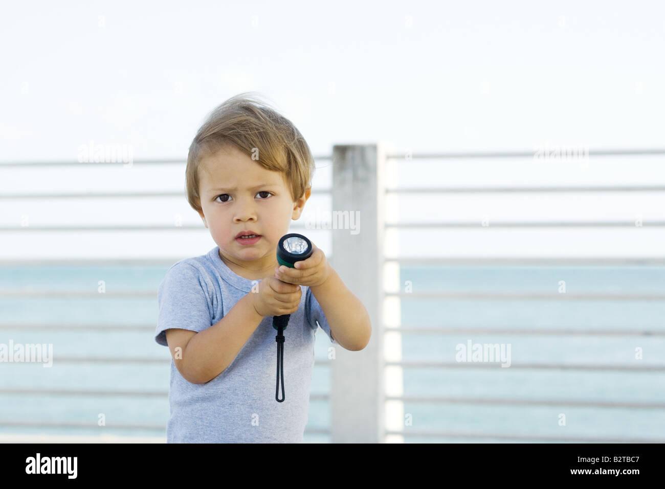 Little boy holding flashlight, frowning at camera - Stock Image