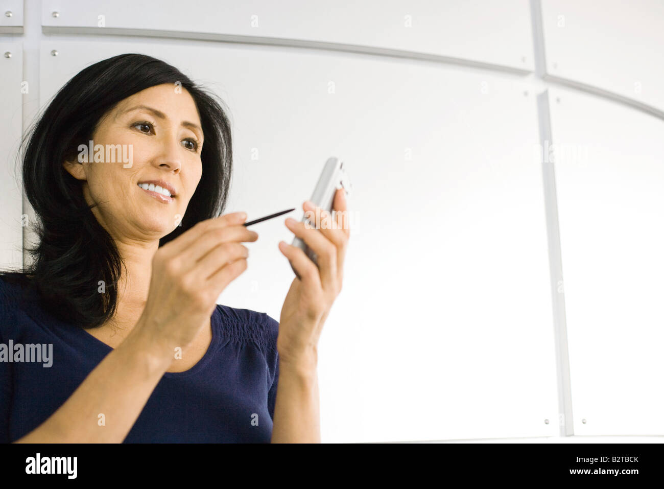 Woman using electronic organizer, smiling, low angle view - Stock Image