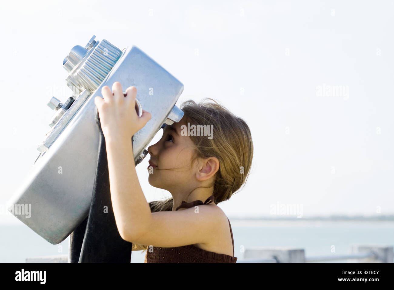 Girl looking through coin-operated binoculars, side view - Stock Image