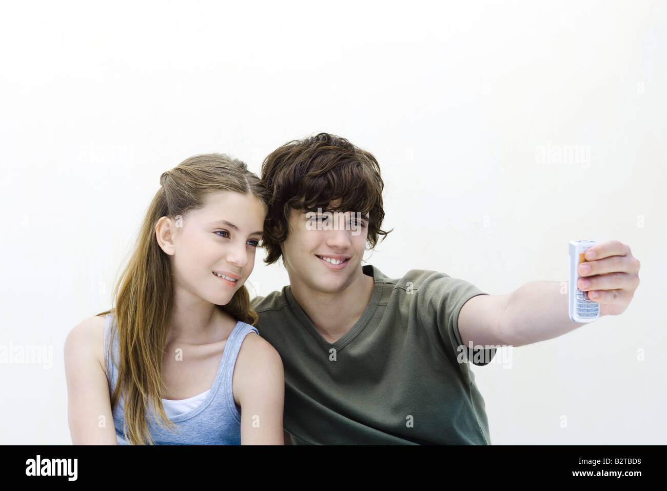 Teenage boy photographing himself and sister with camera phone - Stock Image