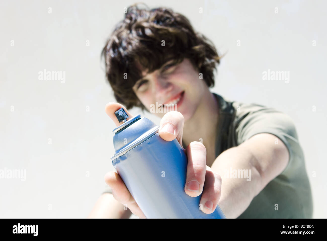 Teenage boy pointing can of spray paint at camera, focus on the foreground - Stock Image
