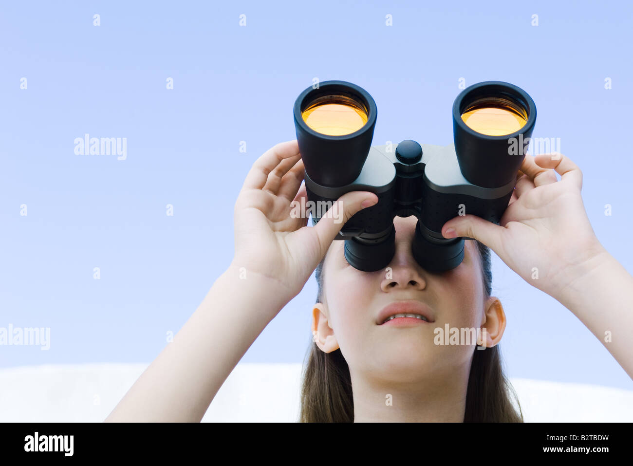 Preteen girl looking up through binoculars - Stock Image