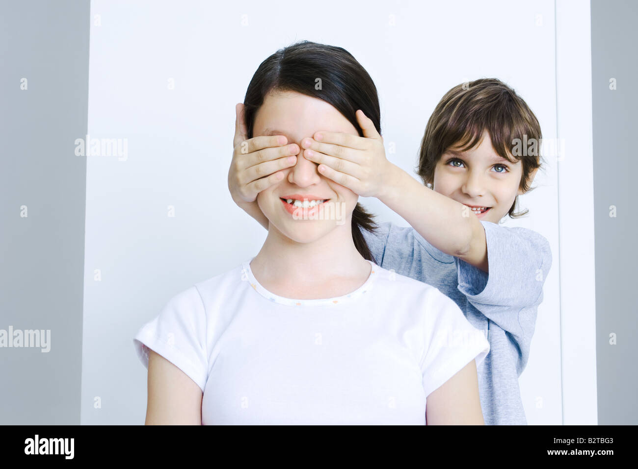 Brother covering his sisters eyes with his hands, smiling - Stock Image