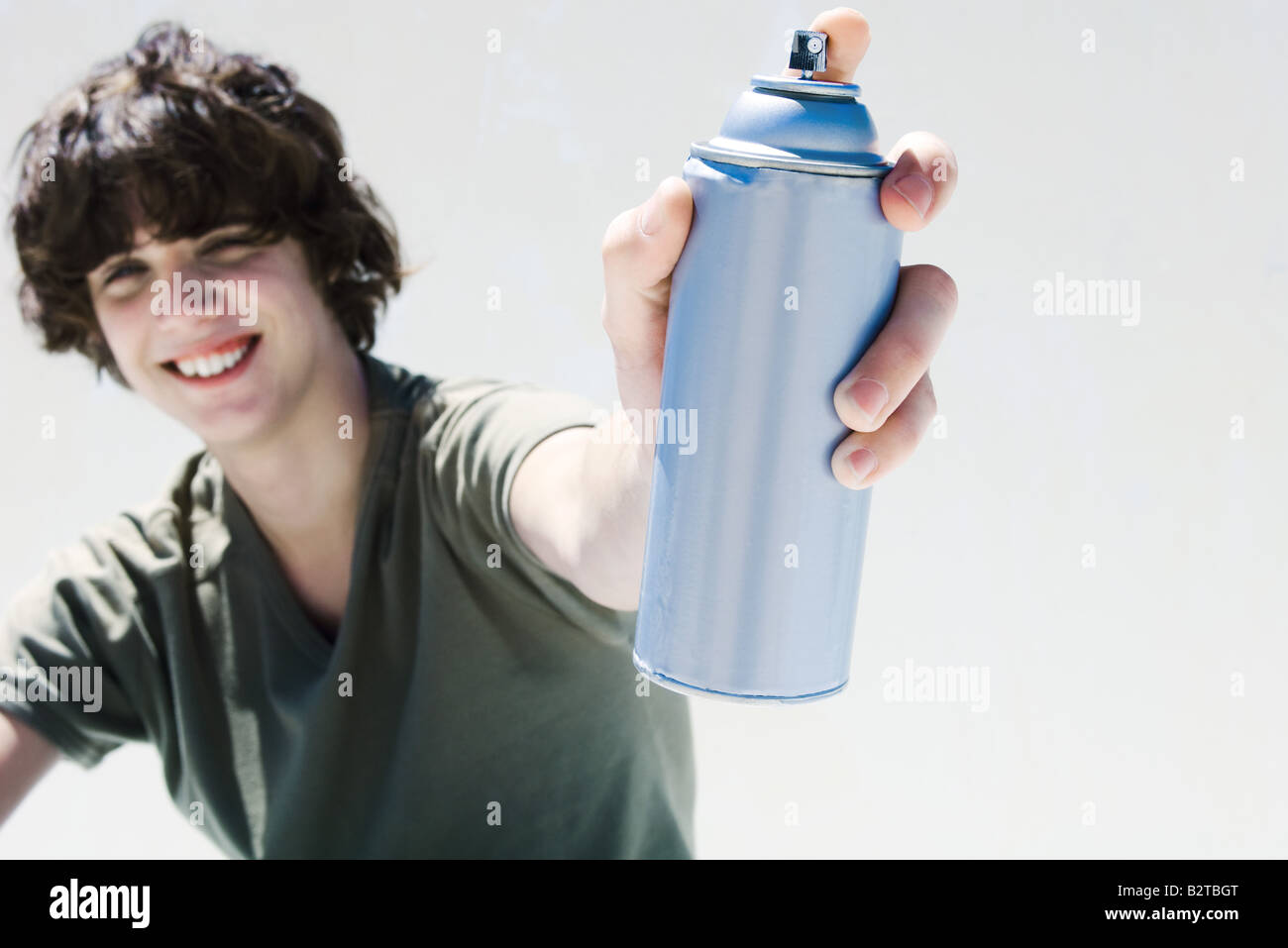 Teenage boy holding can of spray paint, smiling at camera - Stock Image