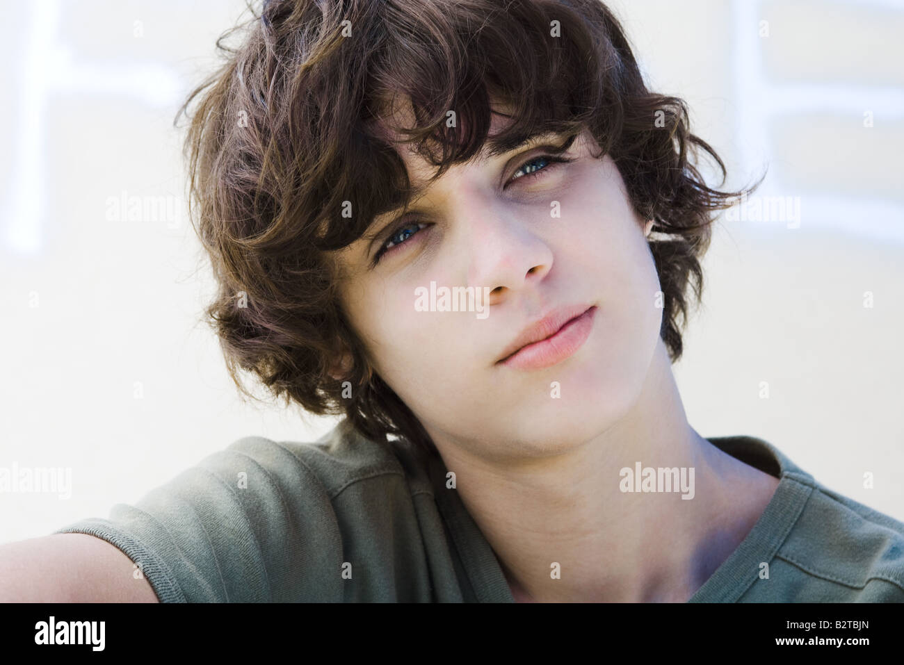 Teenage boy looking away, head tilted, portrait - Stock Image