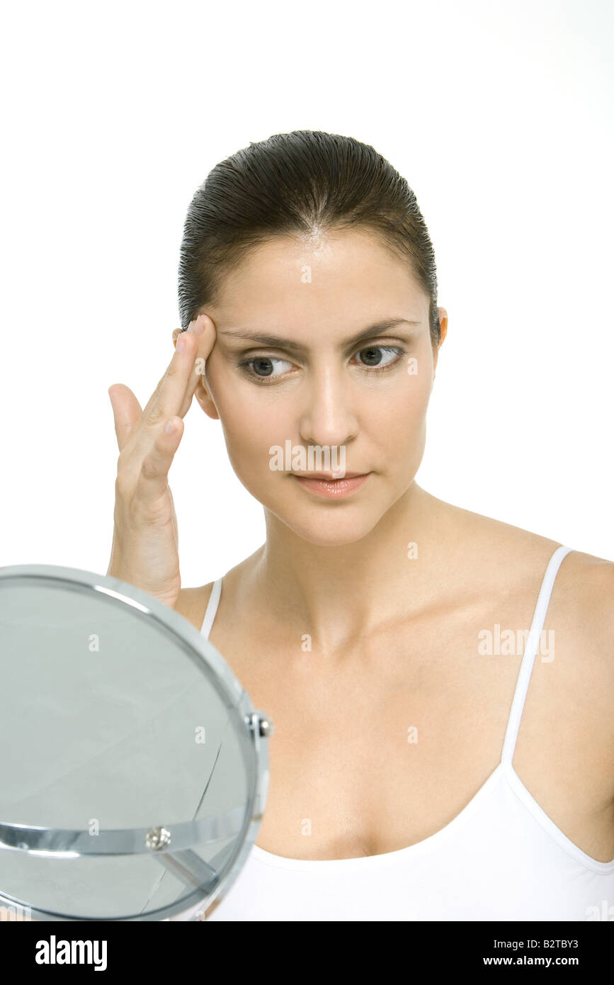 Woman looking at self in mirror, touching temple - Stock Image