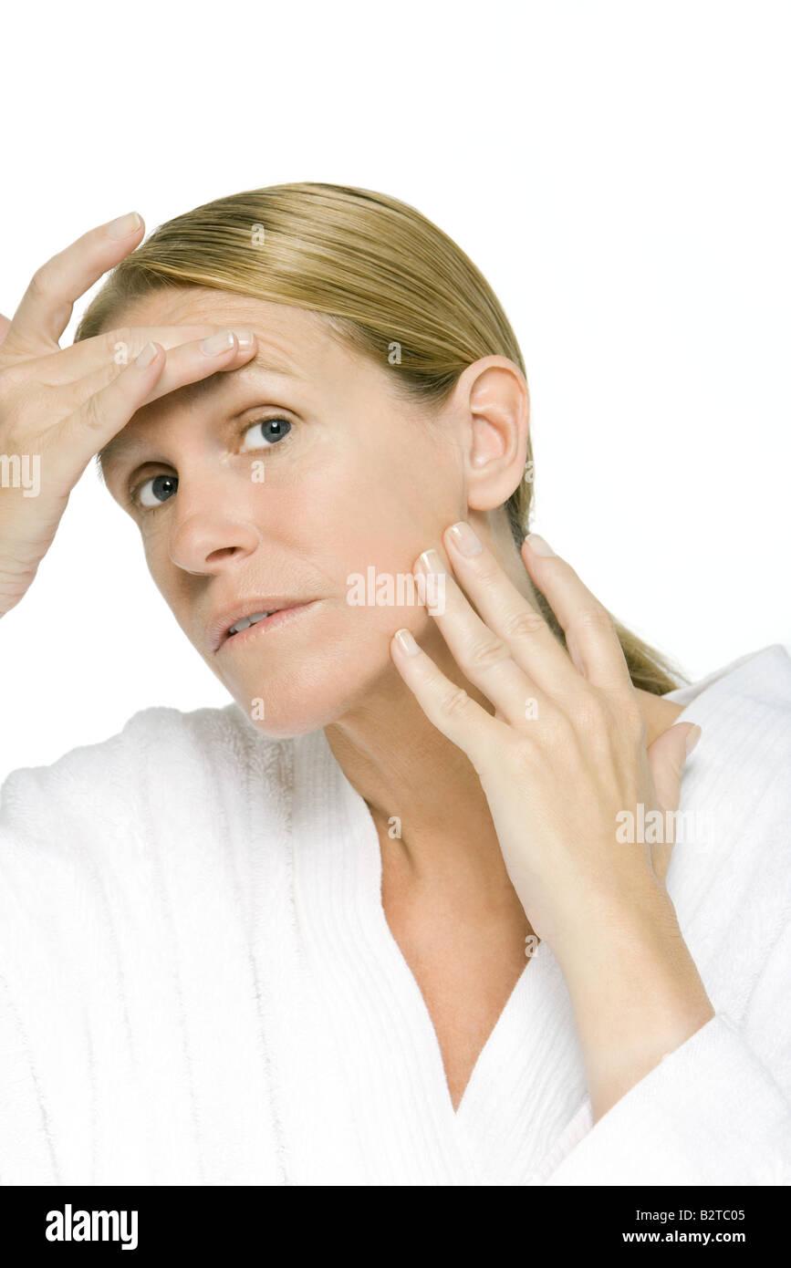 Mature woman examining her face, close-up - Stock Image