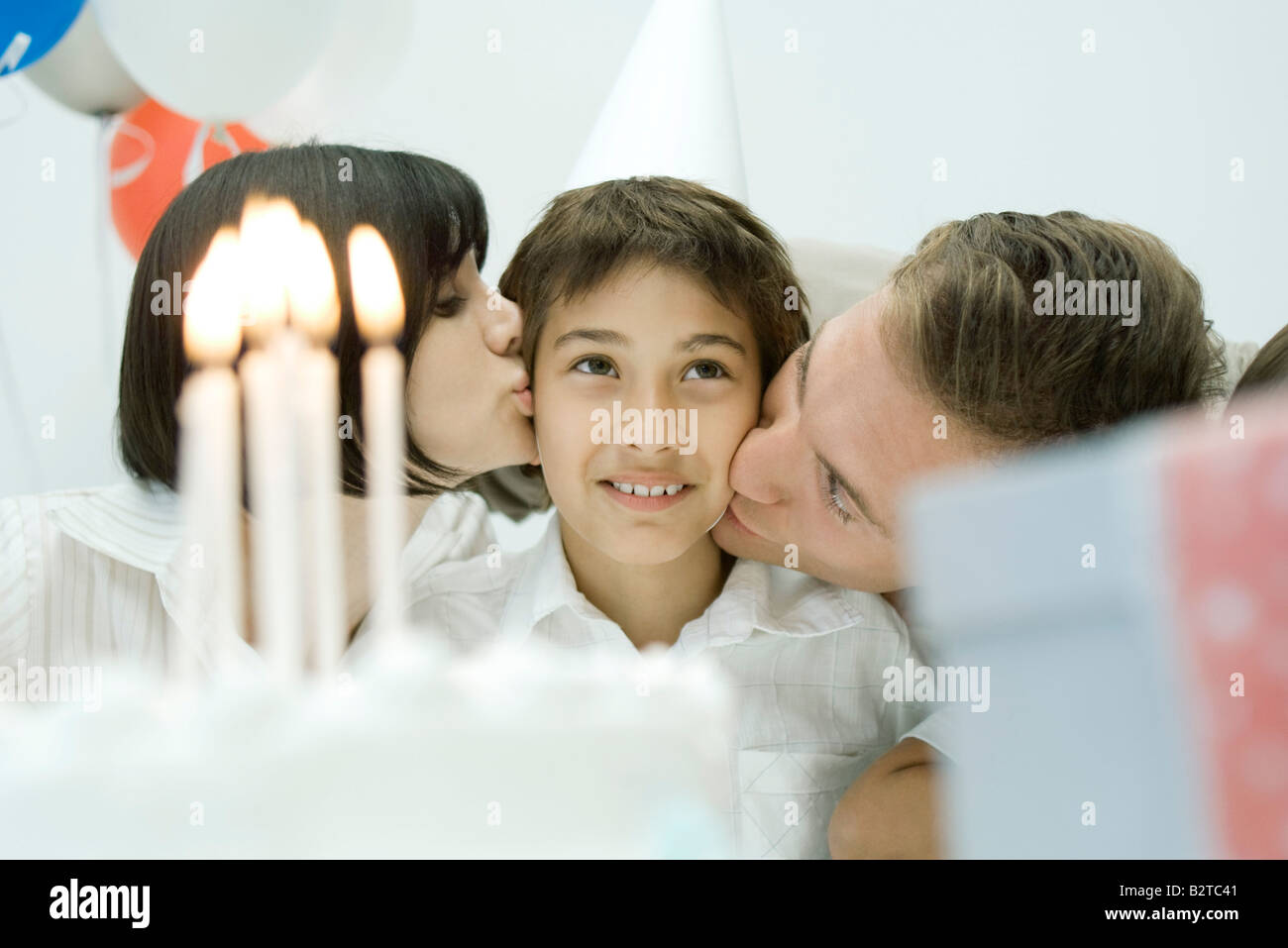 Family behind birthday cake with lit candles, parents kissing boy on cheeks - Stock Image