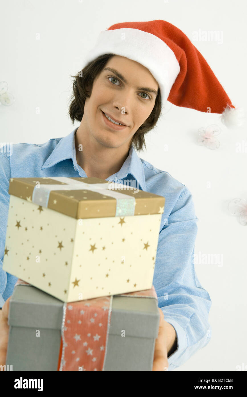 young man holding christmas gifts toward camera smiling