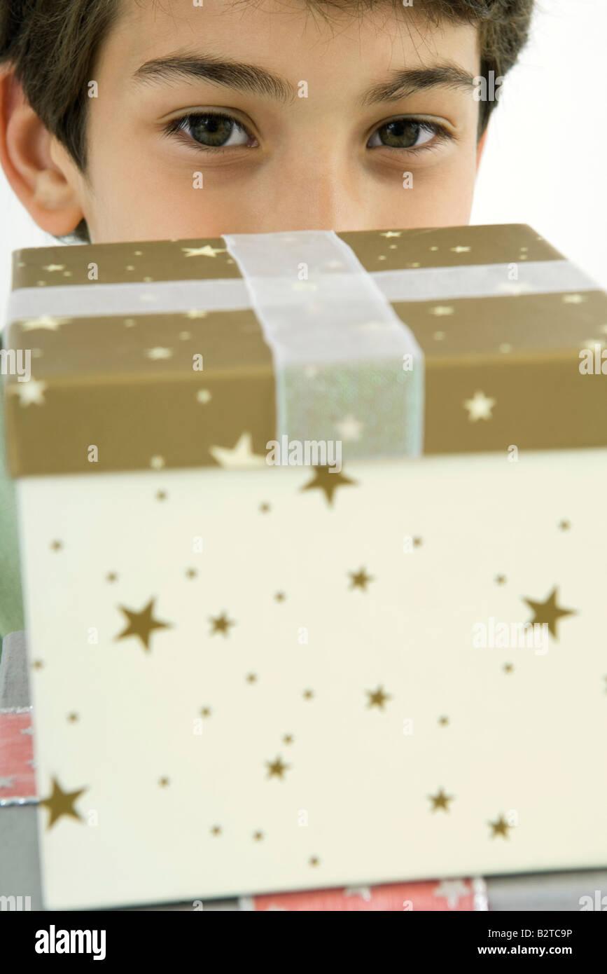 Boy looking over presents at camera, close-up - Stock Image
