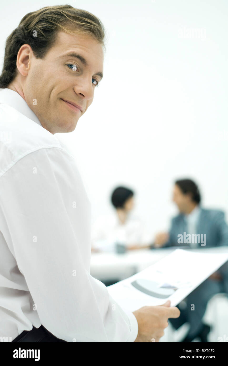 Businessman smiling over shoulder at camera, holding document, colleagues in background - Stock Image
