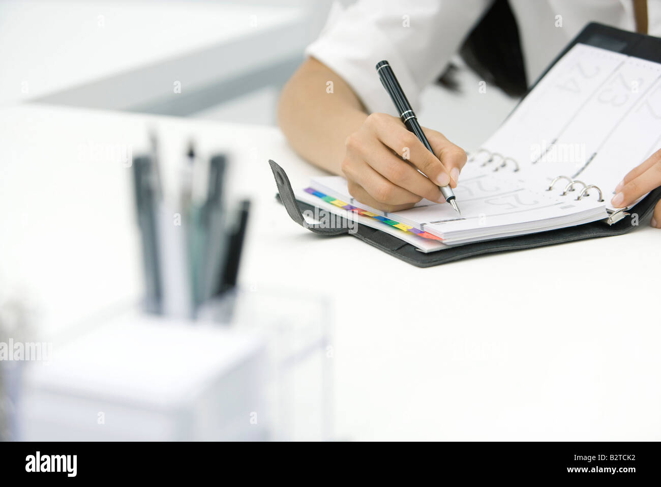 Person writing in agenda, cropped view - Stock Image
