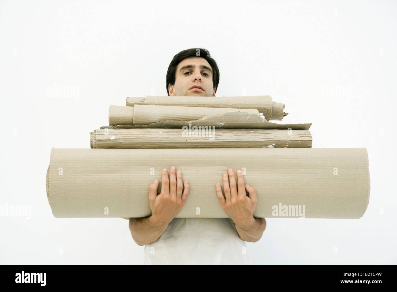 Man carrying large stack of corrugated cardboard, looking at camera - Stock Image