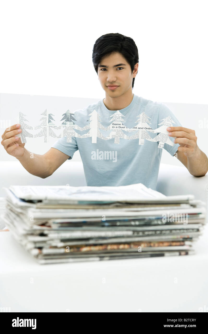 Young man with stacked newspapers, holding tree shapes cut out of paper, looking at camera - Stock Image