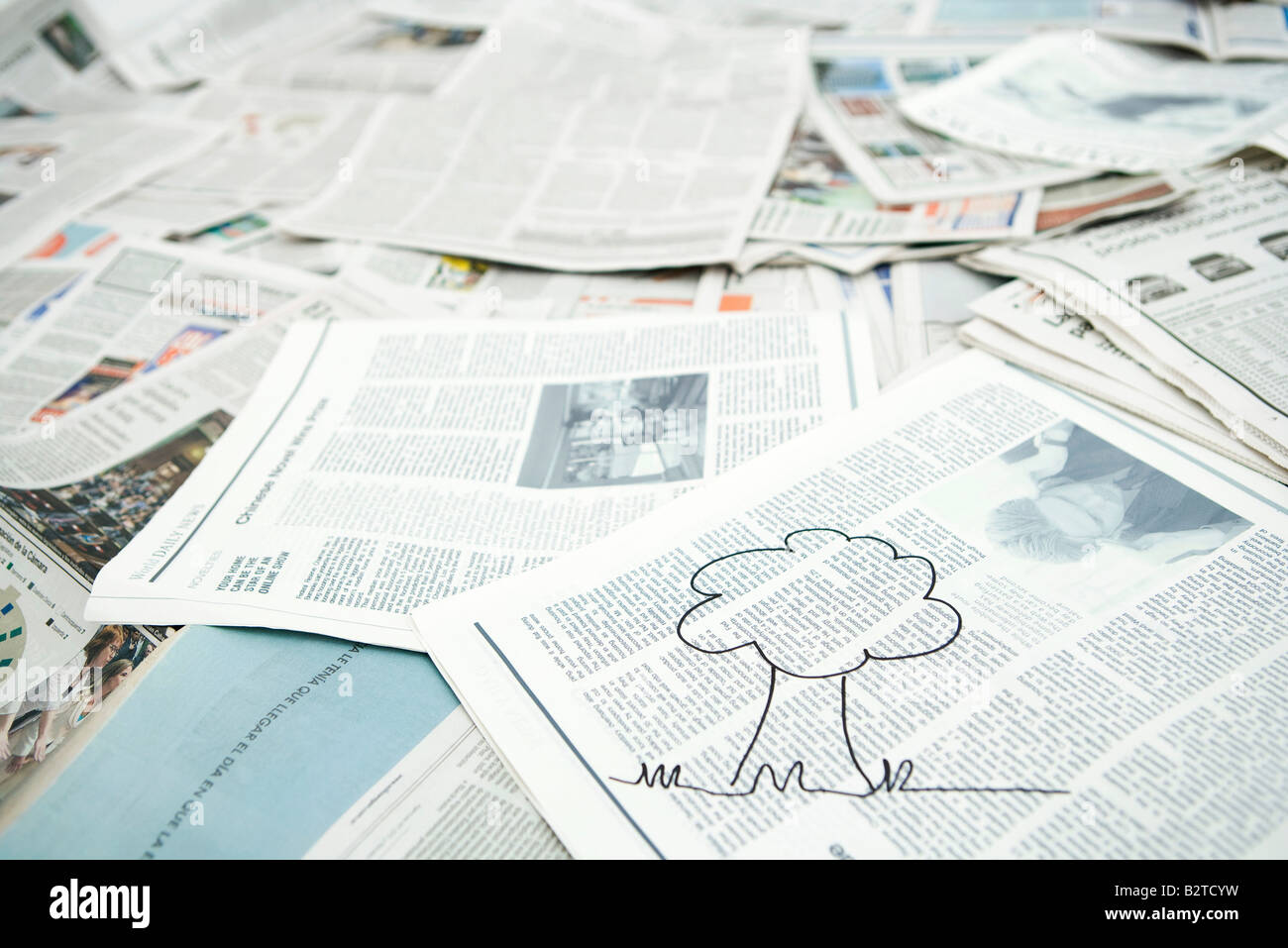 Drawing of tree on pile of newspaper - Stock Image