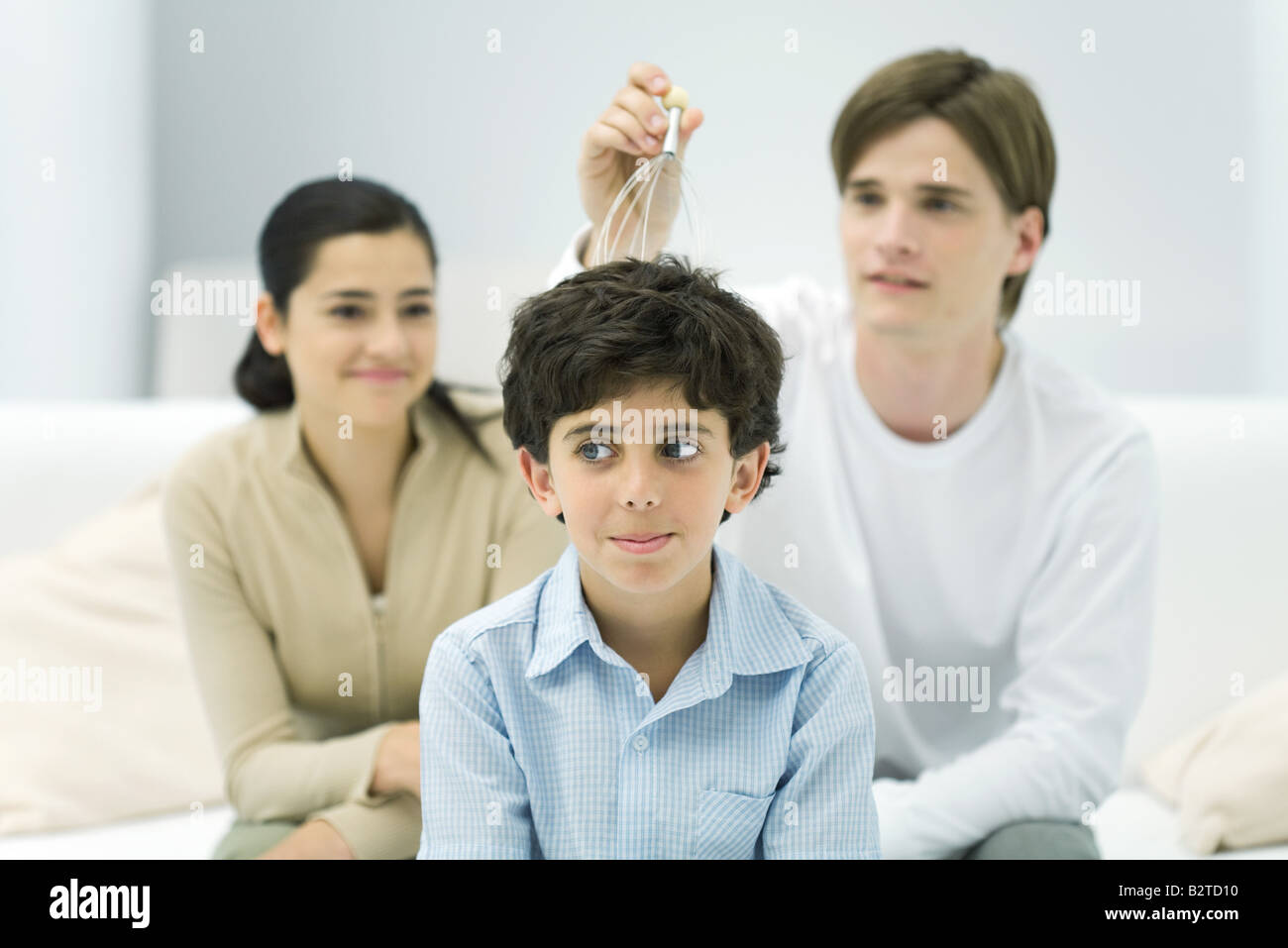 Young man and woman with boy, trying out head massager Stock Photo
