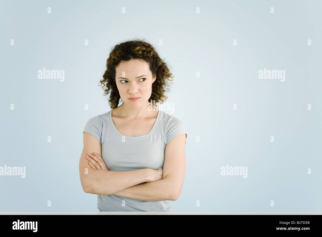 Woman sulking, arms folded, portrait - Stock Image