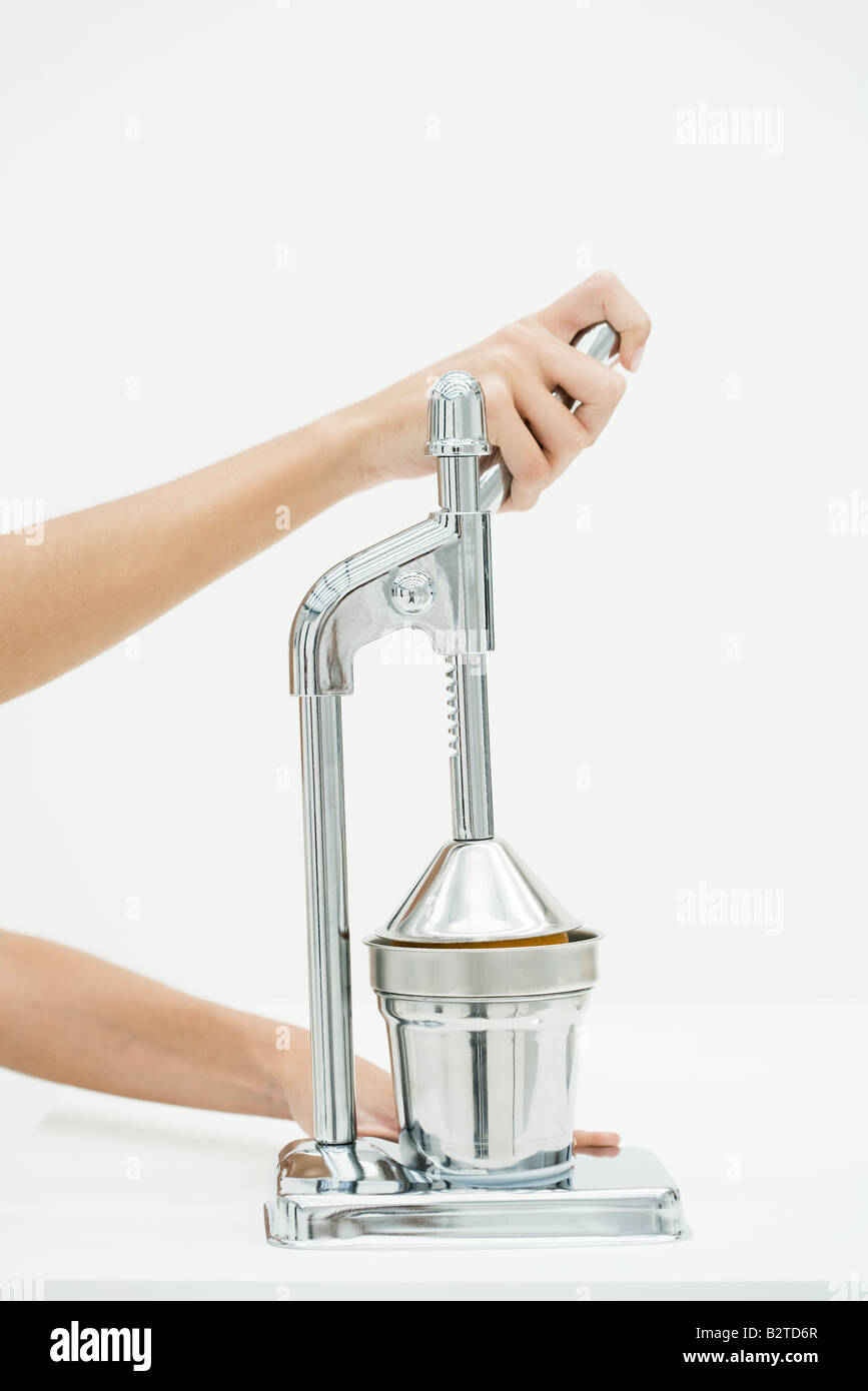 Hand using chrome juicer, cropped view - Stock Image
