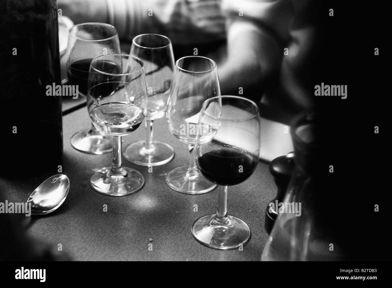 Wine glasses on counter, some empty - Stock Image