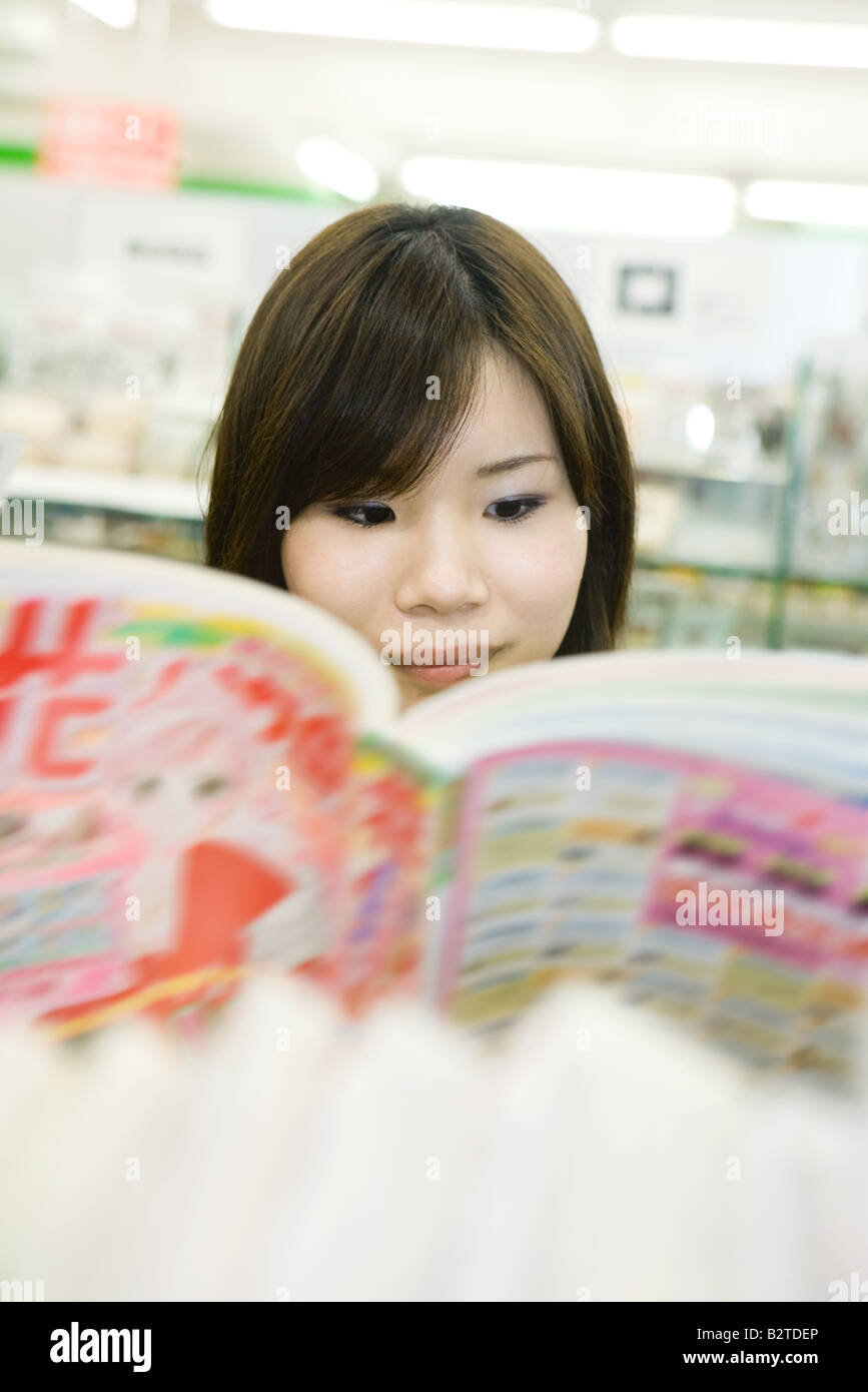 Young Japanese woman reading comic book, selective focus - Stock Image