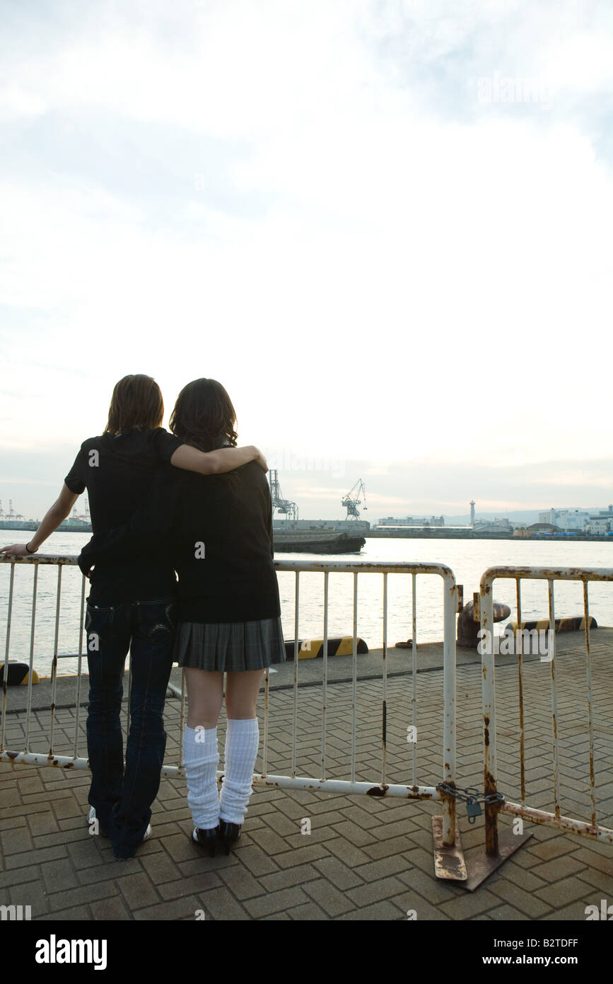Young couple standing together, looking at waterfront, rear view - Stock Image