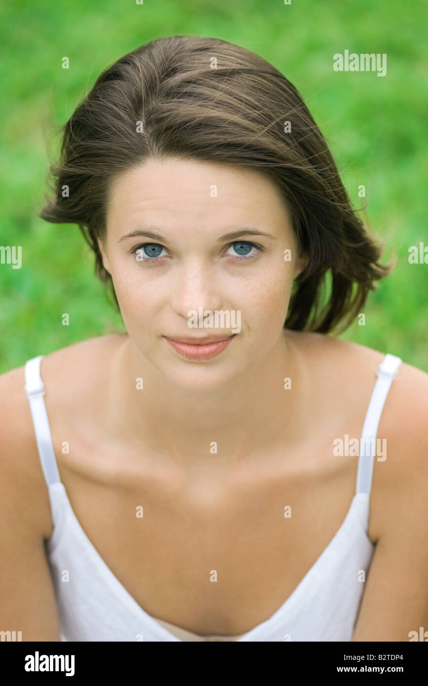 Teenage girl looking at camera, hair tousled by wind, portrait - Stock Image