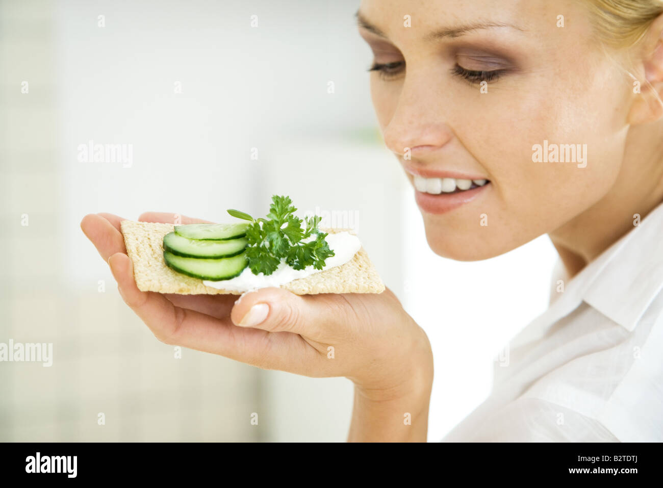 Woman holding up cracker with cucumber slices, smiling - Stock Image