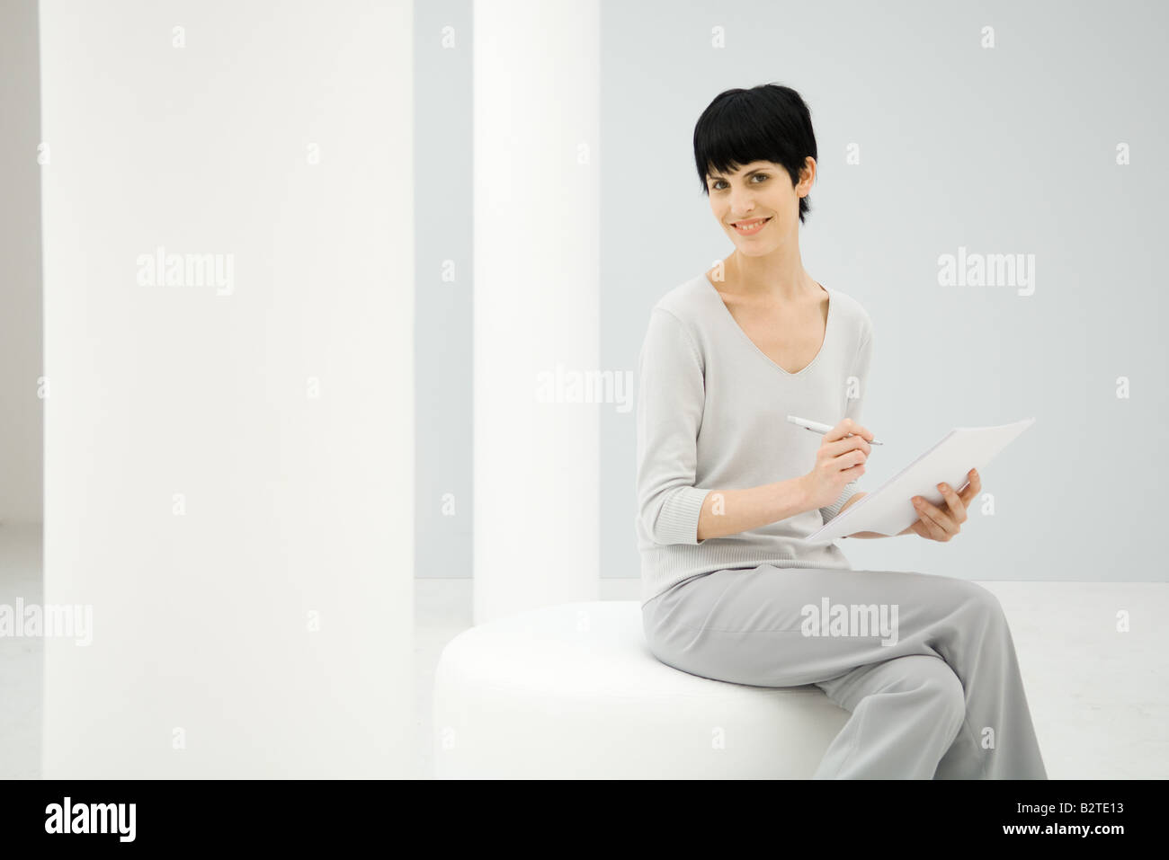 Woman sitting, holding notepad and pen, smiling at camera - Stock Image