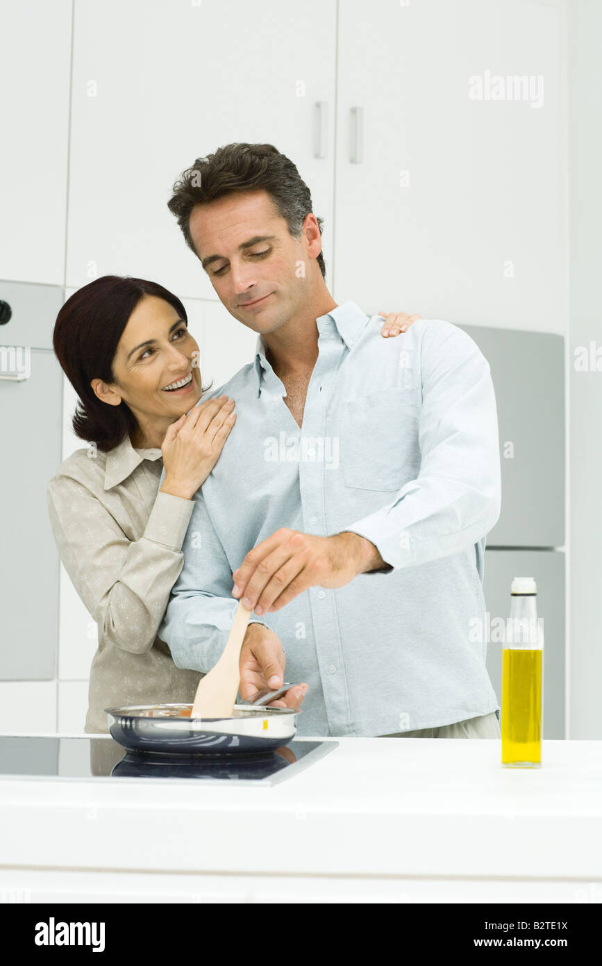 Couple cooking together in kitchen, woman putting hands on man's shoulders - Stock Image