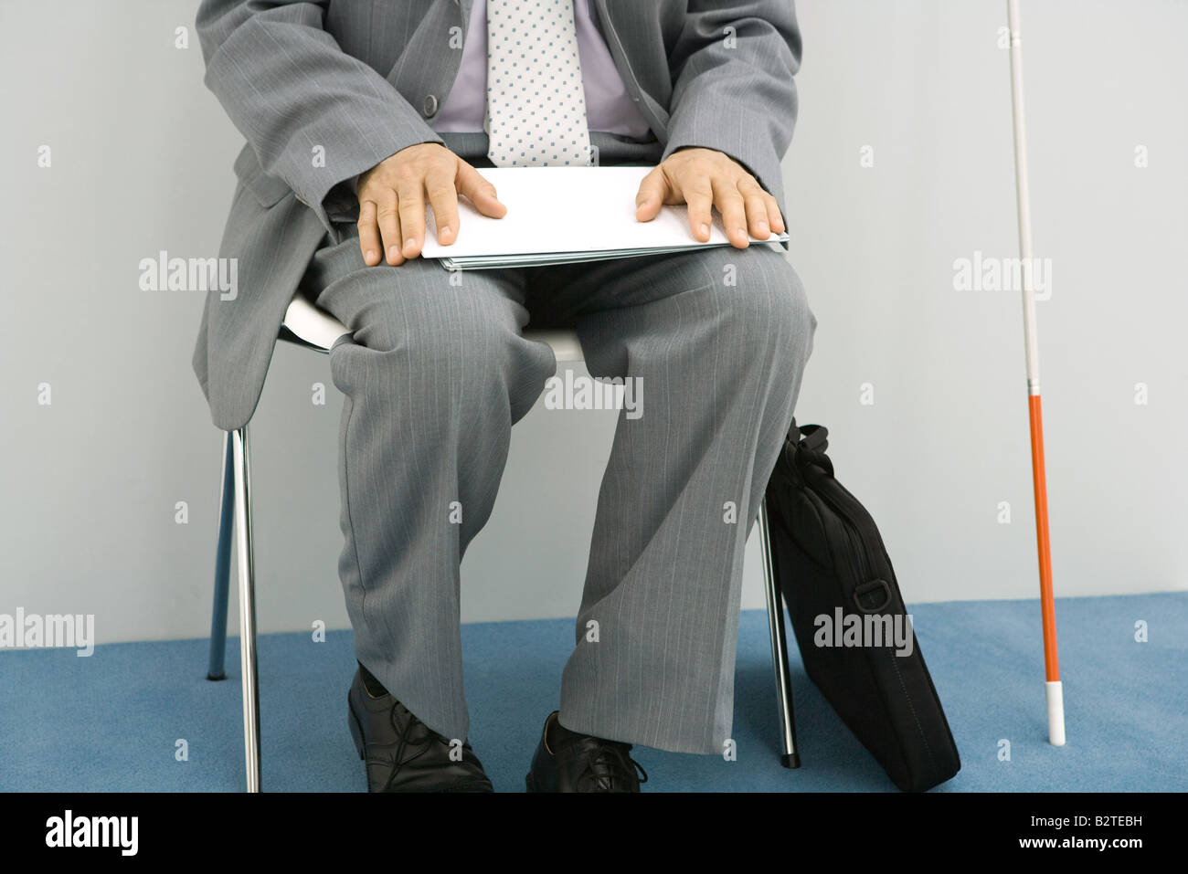 Businessman sitting in chair, white cane propped beside him, holding document, cropped Stock Photo