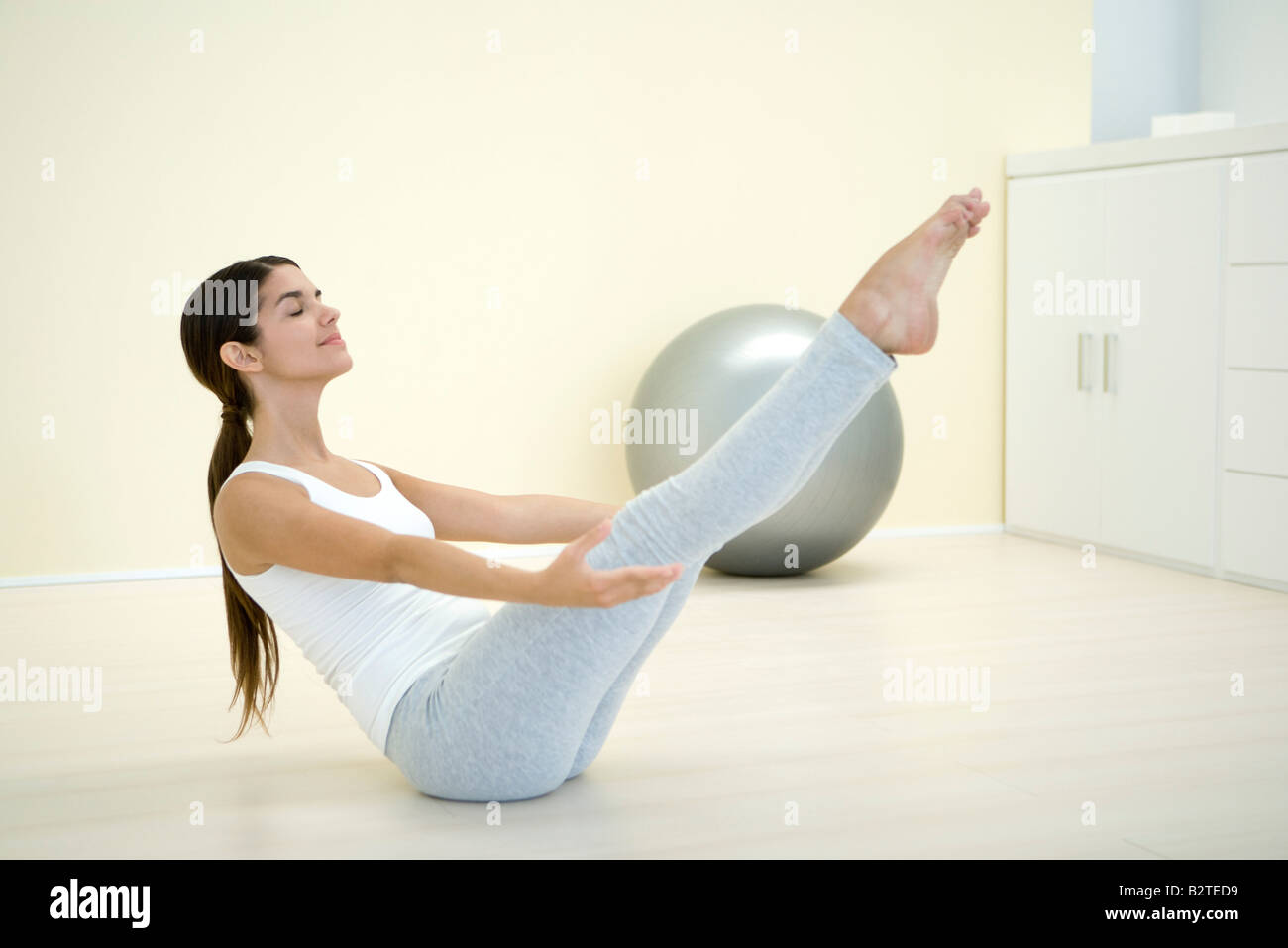 Woman performing boat pose, side view - Stock Image