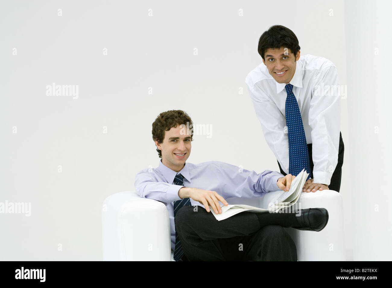 Professional man sitting, holding newspaper, colleague leaning over his shoulder, both smiling at camera - Stock Image