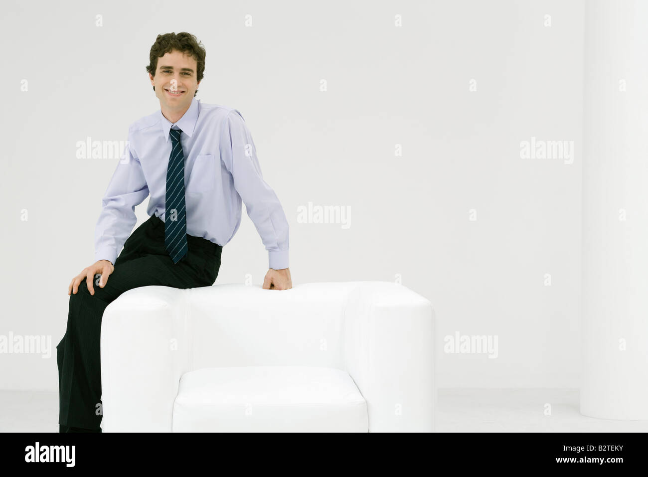 Professional man sitting on armchair, smiling at camera - Stock Image