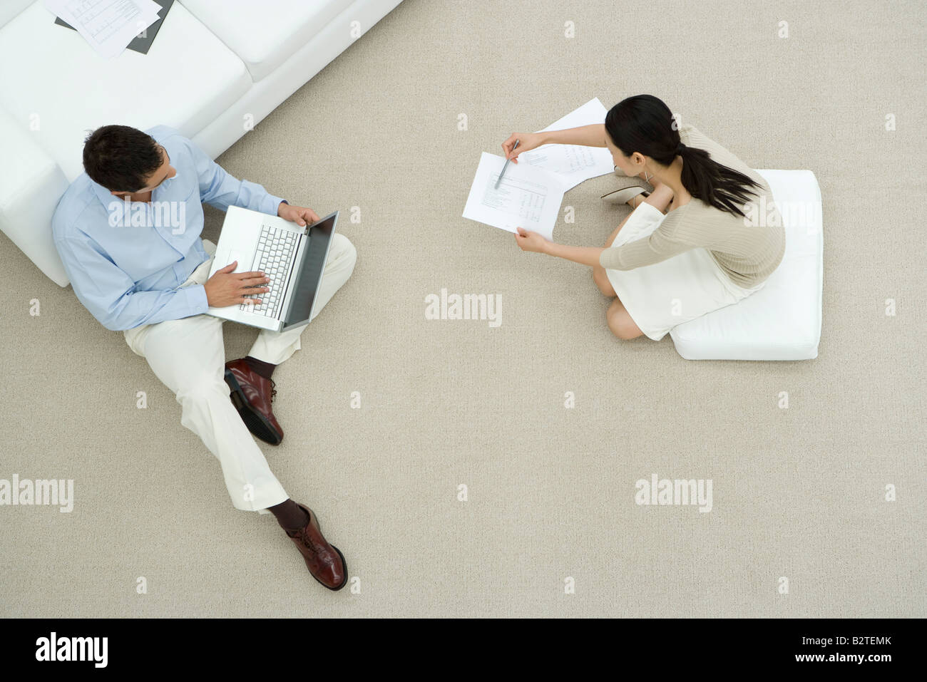 Two colleagues sitting on the ground, discussing document, overhead view Stock Photo