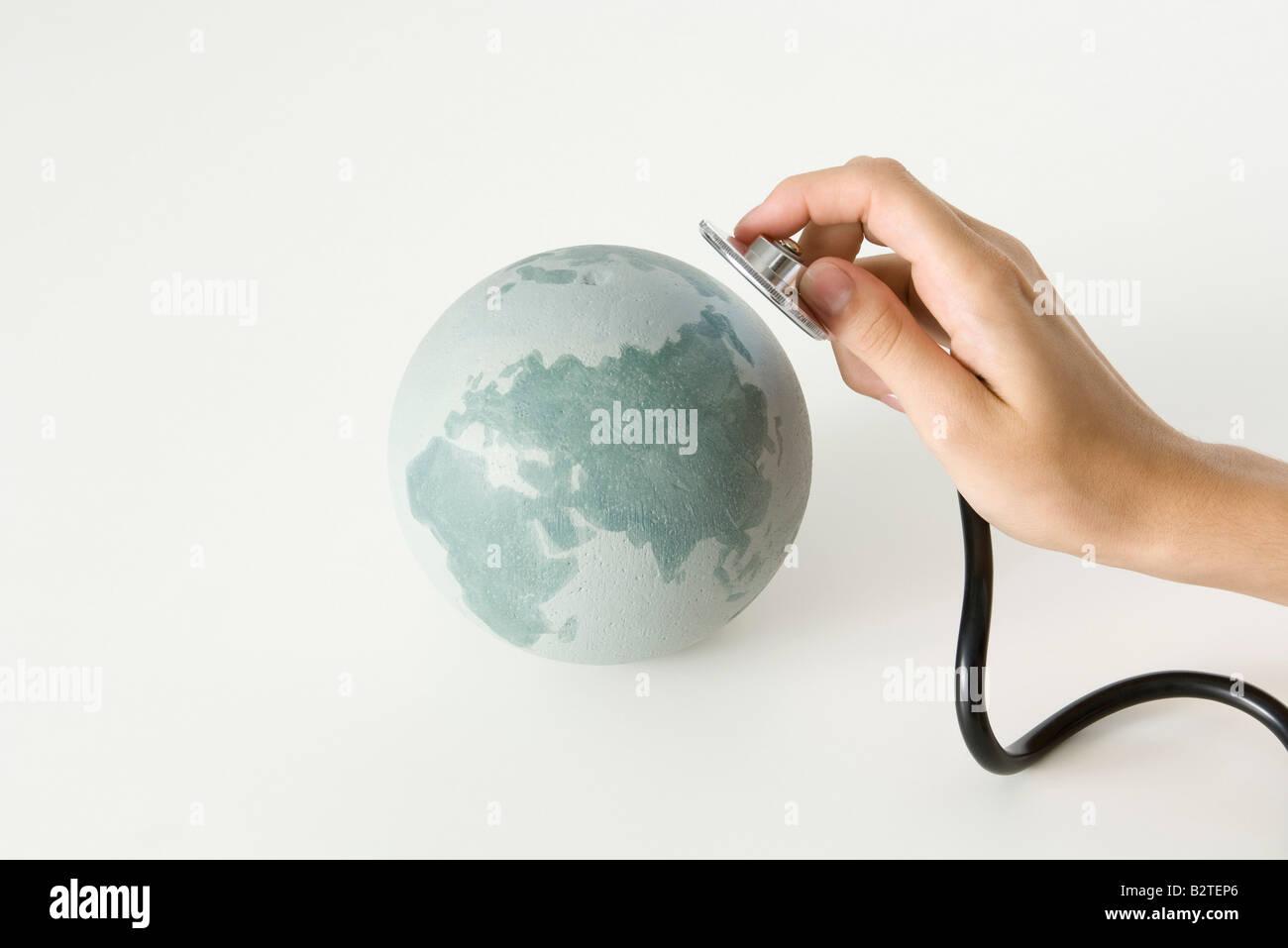 Hand holding stethoscope up to globe, cropped - Stock Image