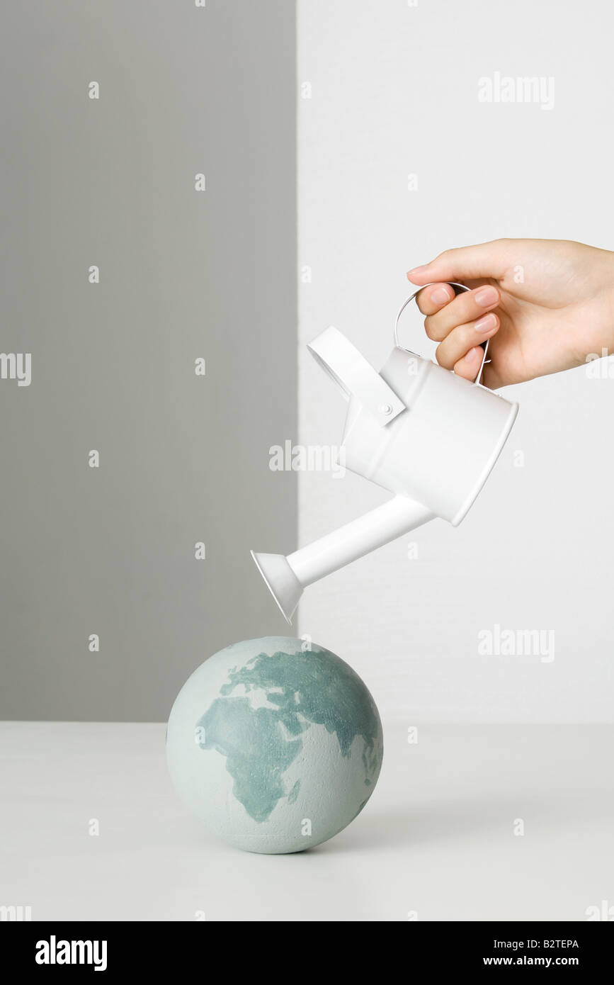 Hand holding watering can over globe - Stock Image