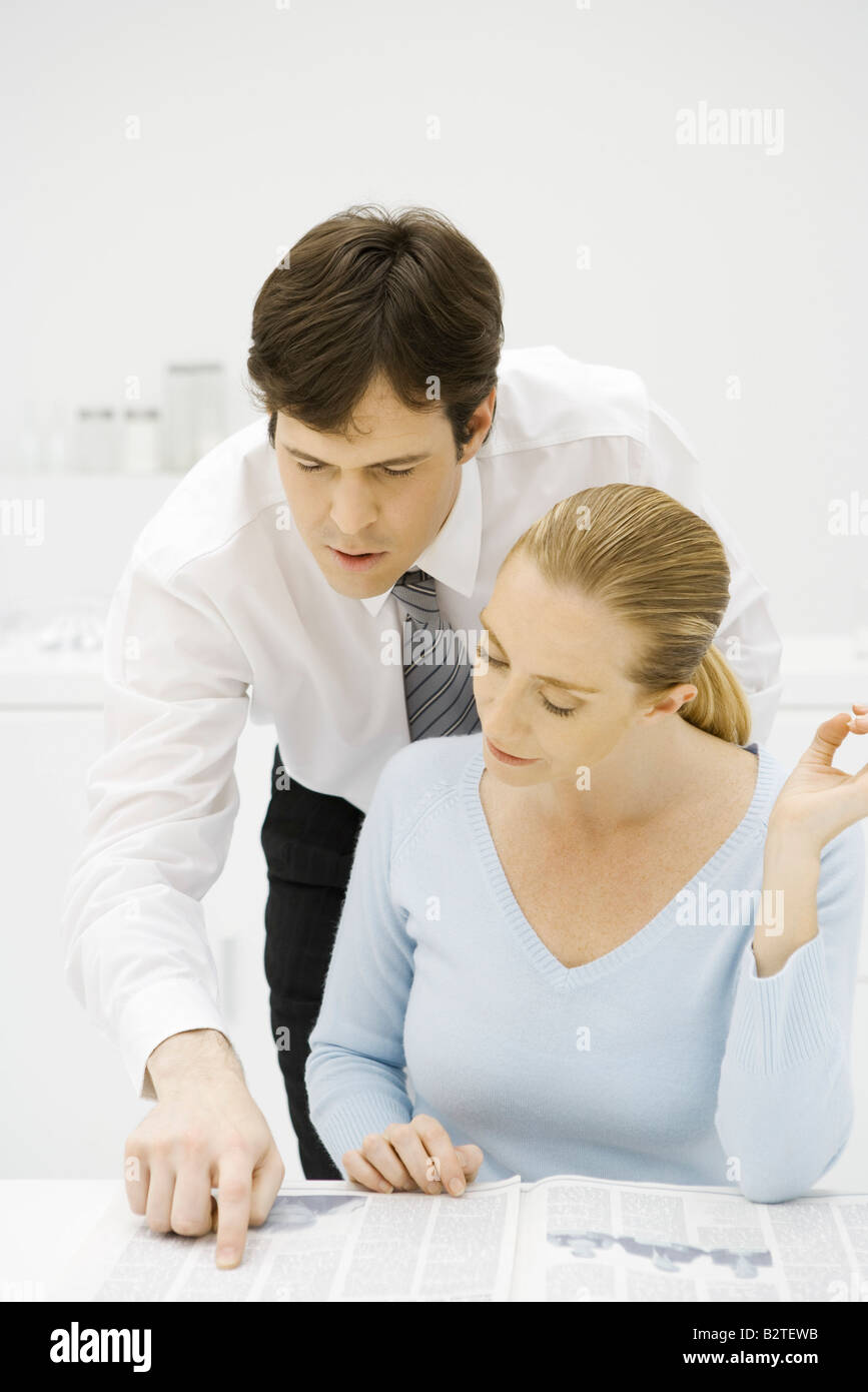 Couple reading newspaper together, man looking over woman's shoulder - Stock Image